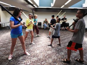 image of children facing each other with practice swords in sword-fighting class