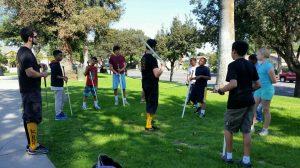 Image of children with pratice swords in outdoor sword-fighting class