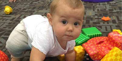 child crawling on colored blocks