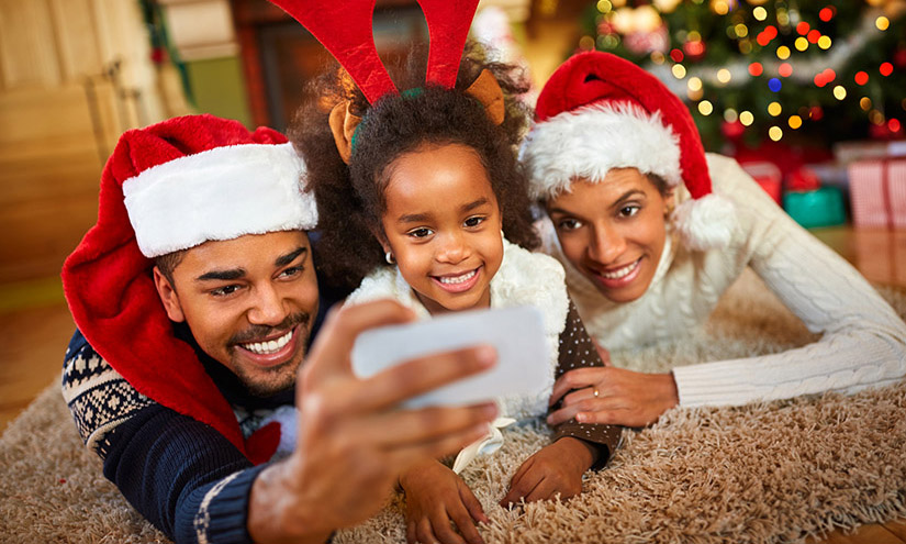 Man, woman and child taking Christmas selfie